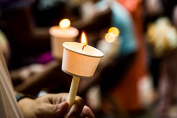 Closeup of people holding candle vigil in darkness seeking hope