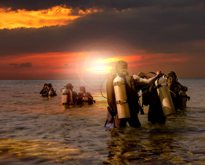 Poster Diving group of scuba diving preparing to night diving at sea side agai