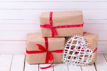 Festive gift boxes and white  decorative heart  on white wooden