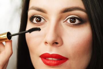 beautiful young brunette woman doing makeup. make up eyelashes