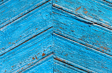 A fragment of a wooden door blue. Painted wooden planks as a background with copy space. Texture old peeling paint, the board of diagonally. Rural background bright blue