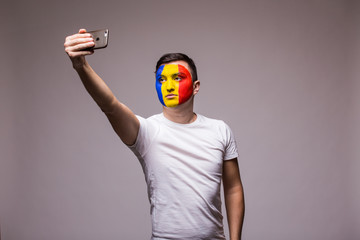 Romanian football fan take selfie photo with phone on grey background. European 2016 football fans concept.