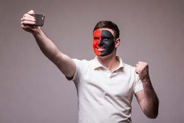 Albanian football fan take selfie photo with phone on grey background. European 2016 football fans concept.