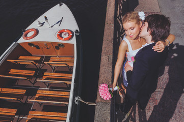 Bride and groom on the background of recreational river boats. View from above.