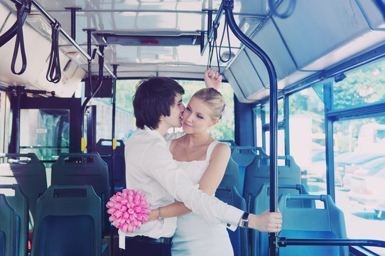 The groom kisses the bride in public transport. Blue bus