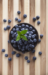 Blueberries in black jar with green leves overhead on wooden cutting board in studio