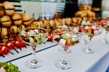 Glasses with Greek salad on reception