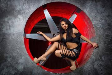 Sexy, provocative studio portrait of a girl on a background of large blades. Woman hunter. Fashion image girl In black lingerie and clothing shreds