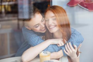 Two cute happy women hugging in cafe