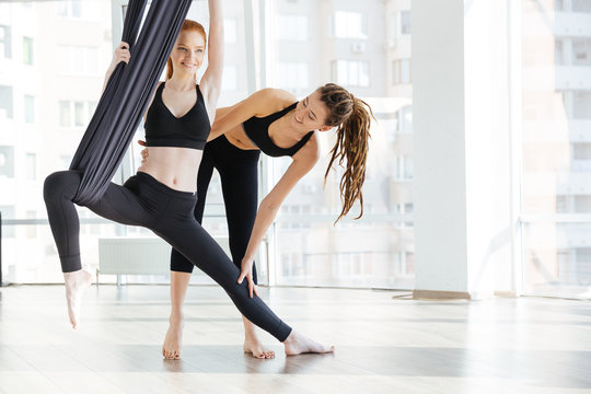 Happy woman doing aerial yoga with trainer in studio