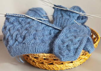 Hand knitting. Hat and mittens with surround pattern in a wicker basket