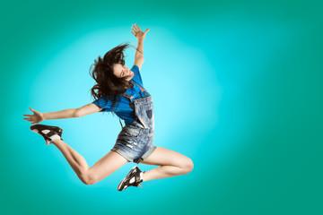 Modern style happy girl dancing on fresh blue background. Hip Hop dancer jumping concept.