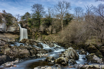 Wide angle view of Thornton Force Waterfall in the Yorkshire Dales National Park with small cascading waterfalls in foreground.
