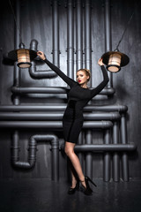 Young, beautiful woman in black dress holding two retro lamps. In the background is the industrial location of pipes