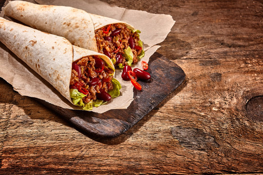 Pair of Chili Stuffed Tex Mex Wraps on Wood Table