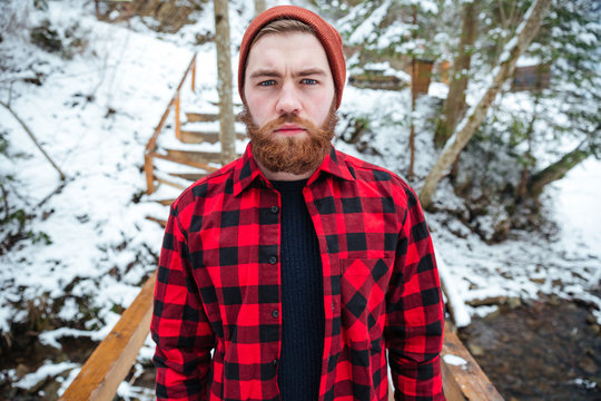 Serious man with beard in plaid shirt at winter forest