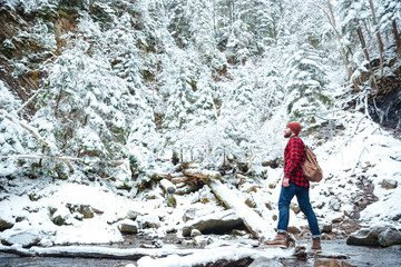 Man with backpack walking near the river in winter forest