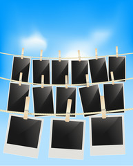 Photo frames hanging on clothesline with clothespins on blue sky