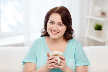 happy plus size woman with cup of tea at home