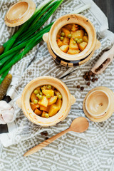 National Russian , Ukrainian and Belarusian cuisine , baked potatoes with meat in the pot , onion , pepper, garlic , pickled cucumber and spices on a wooden background