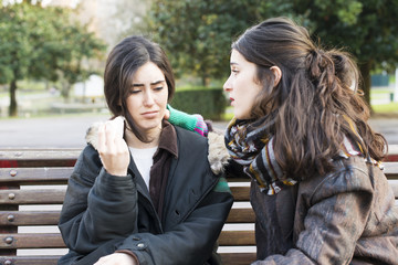 Sad woman crying and friend comforting in the park.