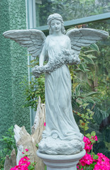 Beautiful image of an angel sculpture holding bouquet of flowers