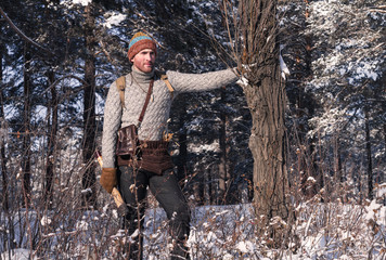 Male tourist and hunter with an ax in the winter forest