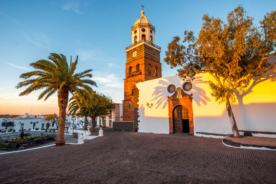 Central square with old church Nuestra Senora de Guadalupe in Teguise village on the sunset on lanzarote island