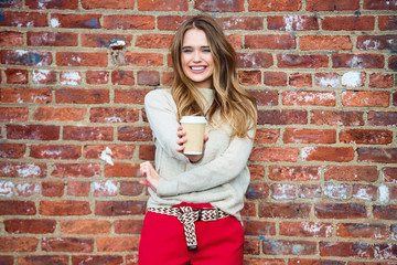 Beautiful happy girl drinking coffee and smiling near red brick wall