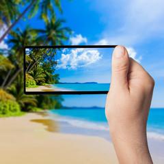 beautiful beach and tropical sea . Taking photo on smartphone