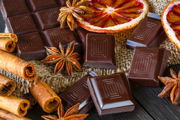 Dark chocolates with dry oranges, cinnamon and anise on burlap on rustic table
