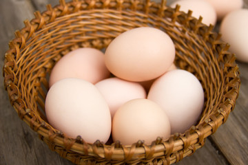Chicken eggs on a wooden table in a wicker basket close-up