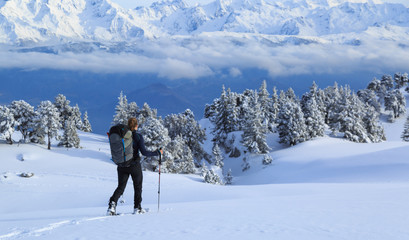 Fotomurales - Female hiker on snowshoes in the snow covered mountains in France during a winter adventure.