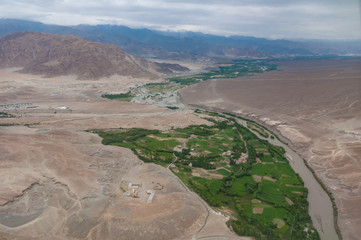 Aerial view of village settlement with small white houses, solitary monastery complex, Indus river and high mountains with stone desert around on the horizon. Leh, capital city of Ladakh region, India