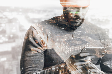 Double exposure of city and man using smart tablet