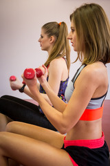 Two young women training with dumbbell at fitness club