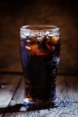 Cola with crushed ice in a big sweaty glass, dark toned image, s