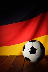 Flag of Germany with football on wooden boards as the background.