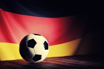 Flag of Germany with football on wooden boards as the background. Vintage Style.