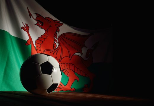 Flag of Wales with football on wooden boards as the background.