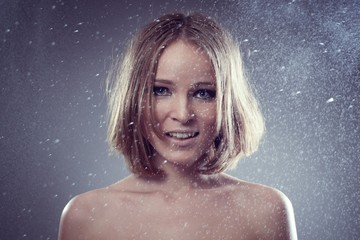 happy attractive woman smiles in rain and catches drops