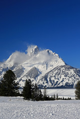 Snow mist blowing off Grand Tetons peaks  in front of snowfield