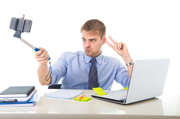 businessman in shirt and tie sitting at office computer desk holding selfie stick shooting self portrait photo