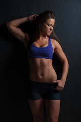 Attractive female fitness model isolated on a black background