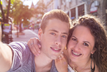 happy young couple doing selfie on street