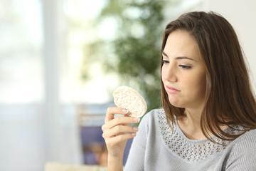 Girl disgusted looking a dietetic cookie