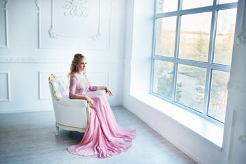 Beautiful blonde woman in evening pink dress posing in studio.Beautiful classic white interior