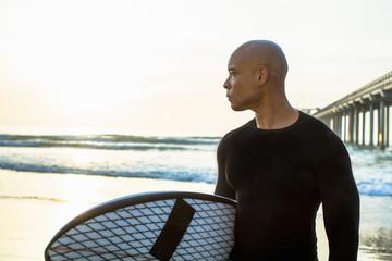 Mixed race man holding surfboard on beach
