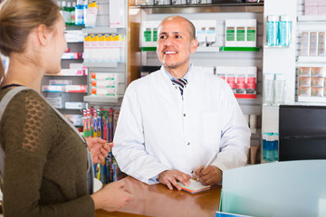 Pharmacist serving client in pharmacy .