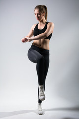 Fitness girl doing stretch exercise. Full length portrait isolated on light background.